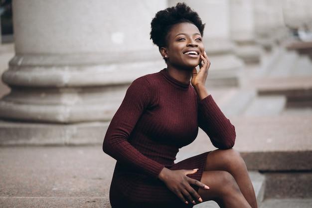 Portrait einer afroamerikanerfrau, die auf treppen sitzt