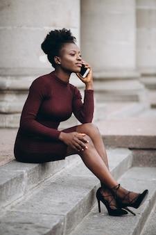 Portrait einer afroamerikanerfrau mit telefon