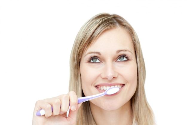Portrait einer attraktiven frau, die ihre zähne putzt