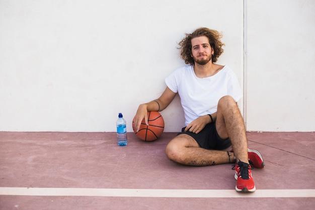 Portrait einer entspannten jungen frau, die mit wasserflasche und -ball sitzt