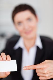 Portrait einer frau, die eine unbelegte visitenkarte zeigt