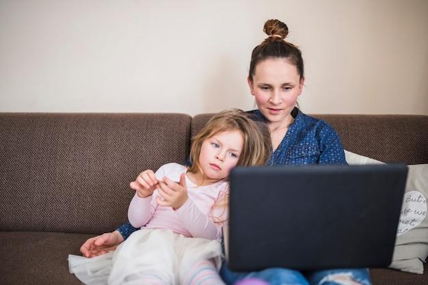 Portrait einer frau, die mit ihrer tochter unter verwendung des laptops sitzt
