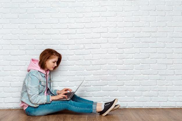 Portrait einer freundlichen frau, die auf dem fußboden mit laptop sitzt