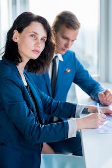 Portrait einer geschäftsfrau, die mit ihrem männlichen kollegen im büro sitzt