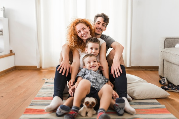 Portrait einer glücklichen familie, die auf bett sitzt