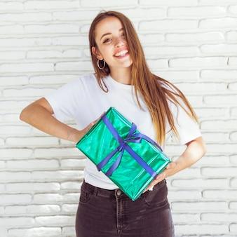 Portrait einer glücklichen frau, die grüne geschenkbox anhält