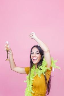 Portrait einer glücklichen frau mit weinglastanzen auf rosafarbenem hintergrund