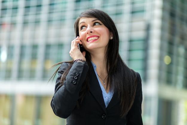 Portrait einer jungen frau, die am telefon spricht