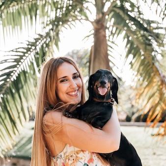 Portrait einer jungen frau mit ihrem hund, der kamera betrachtet