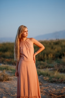 Portrait einer jungen schönen kaukasischen blonden frau in einem rosafarbenen kleid auf einem verlassenen gebiet gegen den sonnenuntergang
