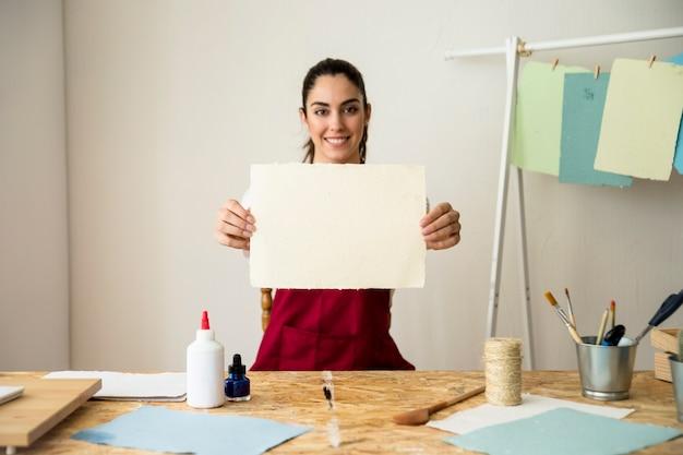 Portrait einer lächelnden frau, die büttenpapier anhält