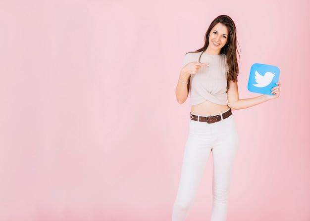 Portrait einer lächelnden jungen frau, die auf twitterikone zeigt