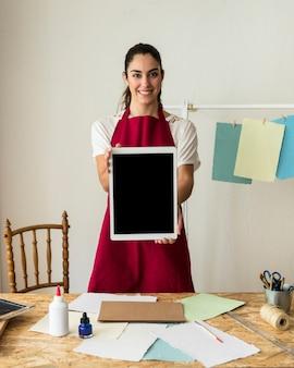 Portrait einer lächelnden jungen frau, die digitale tablette anhält