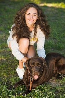 Portrait einer schönen jungen frau mit ihrem hund im garten