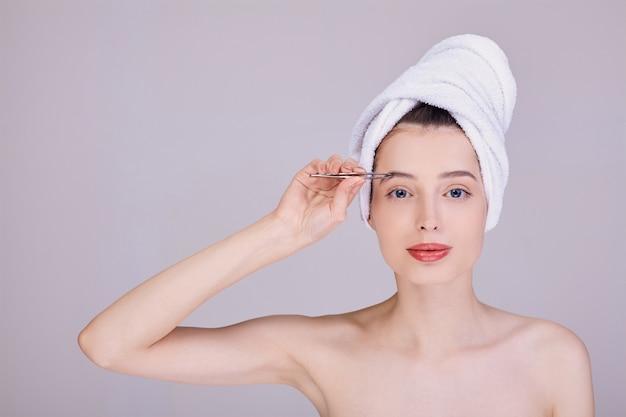 Portrait einer schönheit nach einer dusche, augenbrauen zupfend.