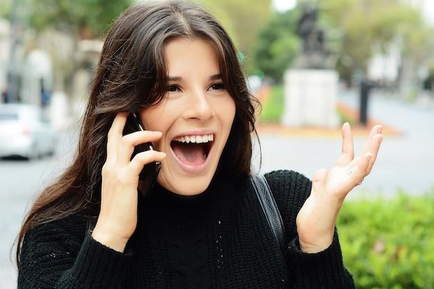 Portrait einer überraschten frau, die am intelligenten telefon spricht