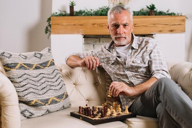 Portrait eines älteren mannes, der auf dem sofa spielt schach sitzt