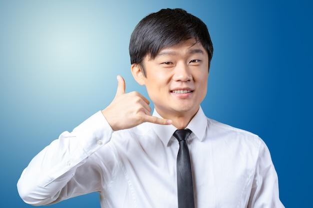 Portrait eines asiatischen geschäftsmannes, der das? anruf ich? symbol zeigt