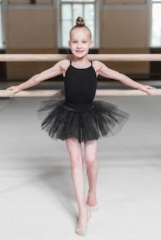 Portrait eines ballerinamädchens im schwarzen ballettröckchen, das vor barre steht