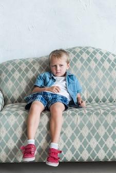 Portrait eines blonden gebohrten jungen, der auf sofa sitzt