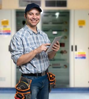 Portrait eines elektrikers, der seinen tablet-computer verwendet