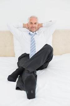 Portrait eines entspannten fälligen geschäftsmannes, der im bett sitzt