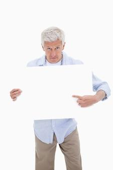 Portrait eines fälligen mannes, der auf ein leeres brett zeigt