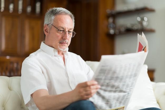 Portrait eines fälligen mannes, der eine zeitung liest