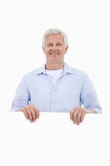 Portrait eines fälligen mannes, der hinter unbelegter verkleidung steht