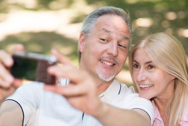 Portrait eines fälligen paares, das ein selfie in einem park nimmt