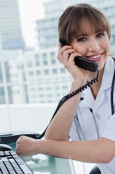 Portrait eines frohen doktors am telefon