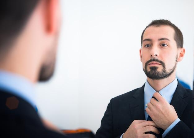 Portrait eines geschäftsmannes, der im spiegel sich betrachtet