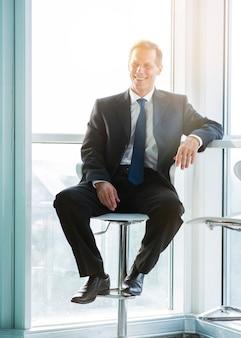 Portrait eines glücklichen fälligen geschäftsmannes, der auf schemel sitzt