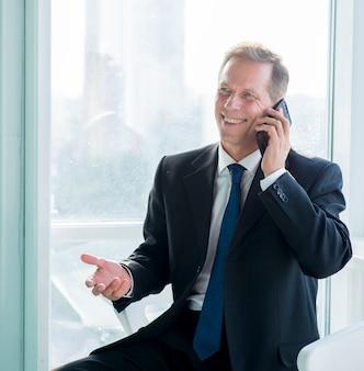 Portrait eines glücklichen geschäftsmannes, der auf mobiltelefon spricht