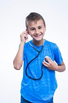 Portrait eines glücklichen jungen, der auf seinen herzschlag mit stethoskop hört