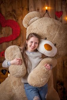 Portrait eines glücklichen mädchens mit einem sehr großen bären