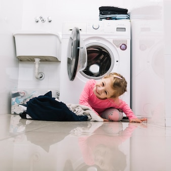 Portrait eines glücklichen mädchens vor waschmaschine