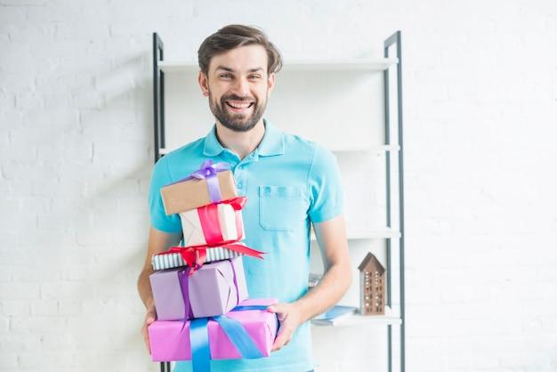 Portrait eines glücklichen mannes mit gestapelten valentinsgrußgeschenken