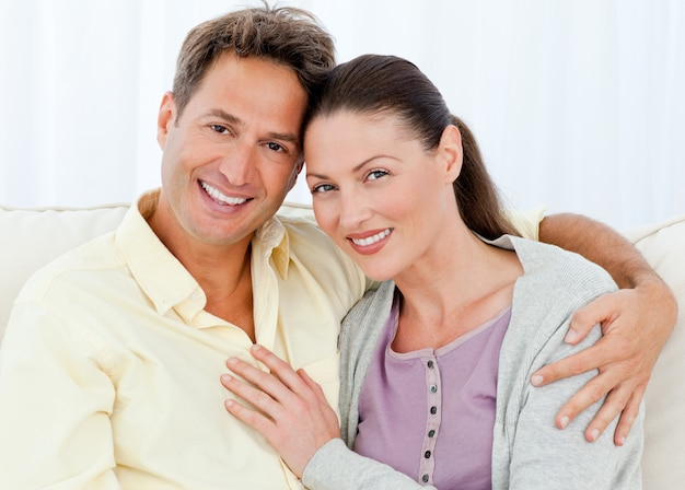Portrait eines glücklichen mannes und der frau, die auf ihrem sofa sitzen