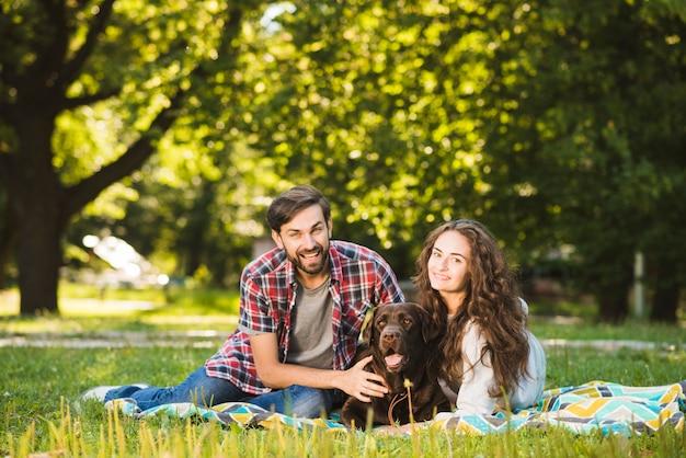 Portrait eines glücklichen paares mit ihrem hund im park