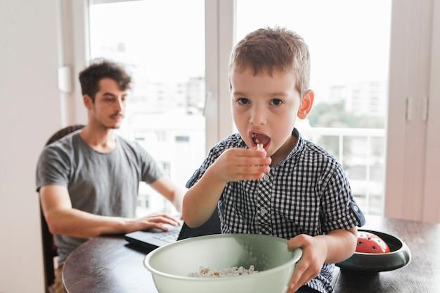 Portrait eines jungen, der auf der tabelle isst popcorn sitzt