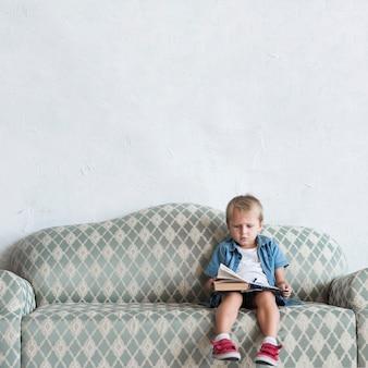 Portrait eines jungen, der auf sofalesenbuch sitzt