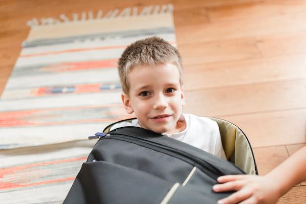 Portrait eines jungen, der im gepäck sitzt
