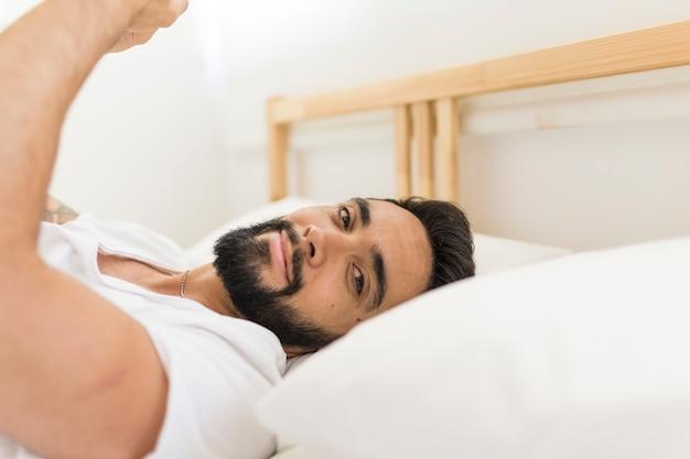 Portrait eines jungen mannes, der auf bett im schlafzimmer sich entspannt