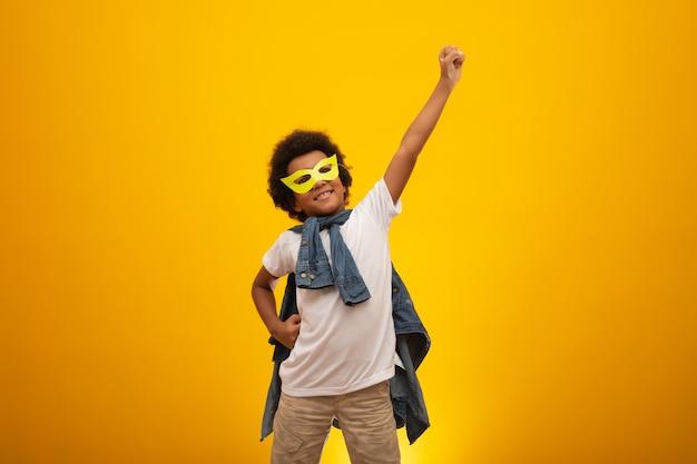 Portrait eines jungen, mischrassejungen gekleidet als superheld. schwarzes baby im superheldkostüm. der gewinner und erfolg
