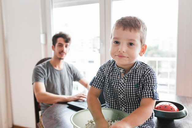 Portrait eines jungen mit dem popcorn, das auf tabelle sitzt