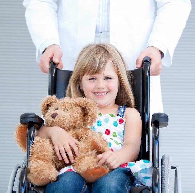 Portrait eines kleinen mädchens, das auf dem rollstuhl unterstützt von einem männlichen doktor sitzt