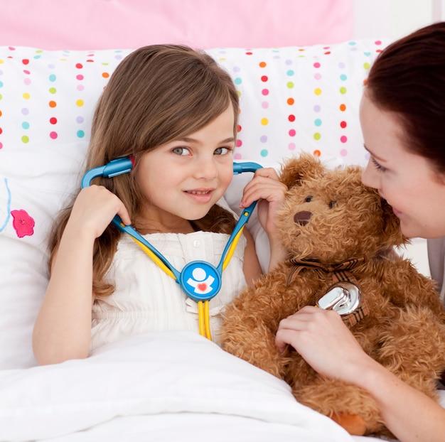 Portrait eines kleinen mädchens, das mit einem stethoskop spielt