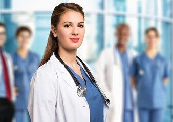 Portrait eines lächelnden Doktors vor einer Gruppe Kollegen