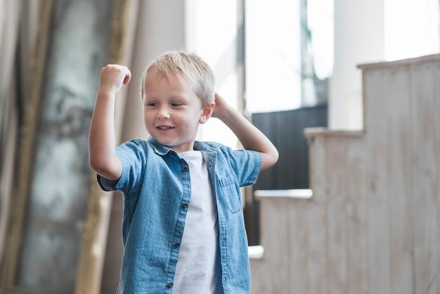 Portrait eines lächelnden jungen, der seinen muskel biegt
